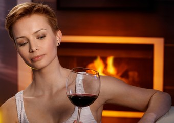 Young woman studying glass of wine