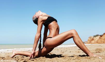 Beautiful slim woman doing yoga at the beach