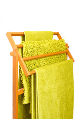 Green towels hanging on a wooden towel rail isolated