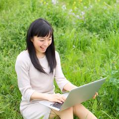 ノートパソコンを外で使う女の子