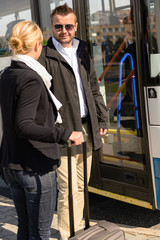 Woman and man talking in bus station