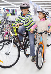 Boy and girl in helmets sit on bright bicycles