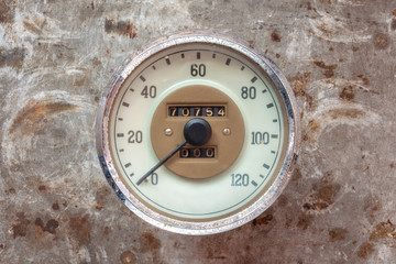 Vintage car speedometer on a rusty background