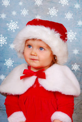 cute baby in santa hat with snow flakes