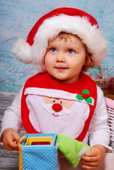 cute baby in santa hat playing with toys