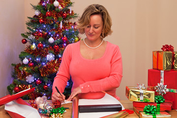 A woman at home wrapping Christmas presents