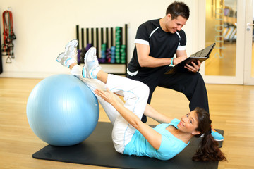 Personal trainer instructing woman in gymnastics