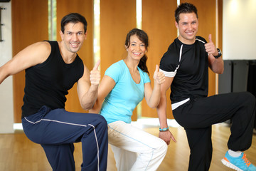 Three people doing aerobics in a gym