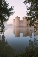 Stunning moat and castle in Autumn Fall sunrise with mist over m