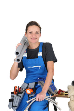 Female plumber with various tools and materials