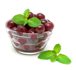 frozen cherries and mint sprigs on a white background