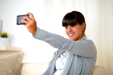 Young woman taking a photo with cellphone at home