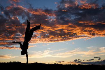 Wall Mural - silhouette of kid doing one handed handstand in sunset