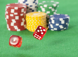 Rolling red dice on a casino table with chips