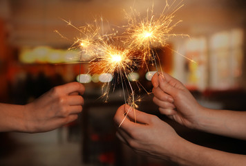 beautiful sparklers in woman hands on room background.