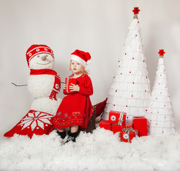 Little cute girl in Christmas red dress and Santa hat