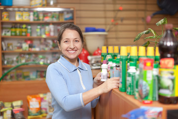 woman chooses agricultural chemicals in the store