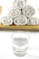 rolled white towel and water, glass