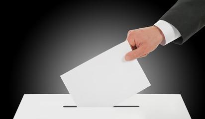 Man hand down ballot in the ballot box
