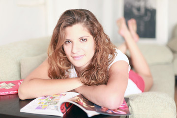 Hübsches Mädchen liegt auf dem Sofa und liest