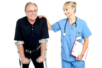 Cheerful doctor encouraging her patient to walk with crutches