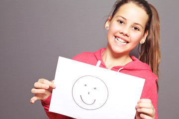 Happy young girl holding smiley