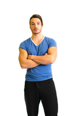 Attractive and fit young man standing, arms crossed