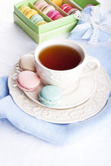 Cup of tea with colorful french macarons