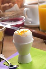 Breakfast of boiled egg, coffee, orange juice, croissant,  jam a