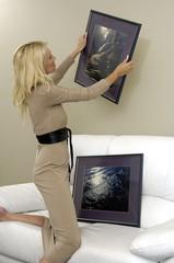Frau hängt Bilder auf