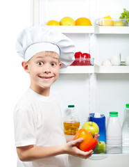 cute cook boy is choosing food near the open refrigerator