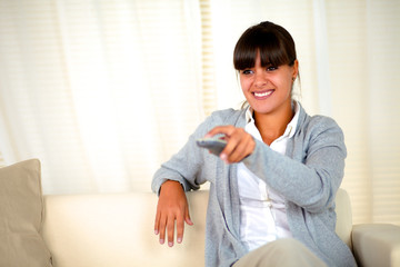 Smiling young woman using a tv remote
