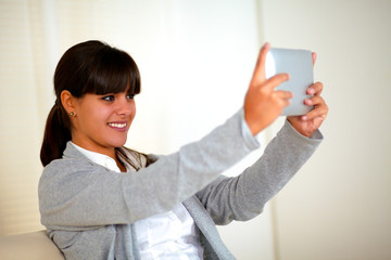Smiling young woman taking picture with tablet pc