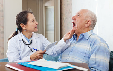 mature doctor looks the mouth of  patient