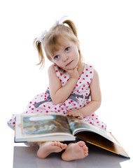 dreaming baby girl reading a book. isolated on white