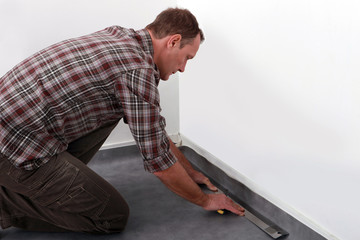 Tradesman laying down linoleum flooring