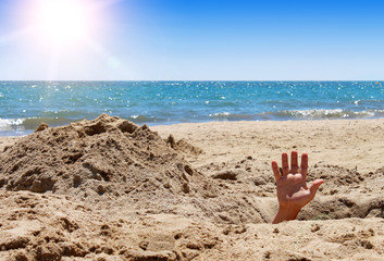 Man's hand out of the hole on the sandy beach