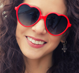Fun smiling woman in silly red heart love sunglasses