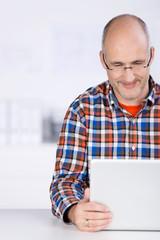 mann im büro schaut auf seinen laptop