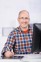 lächelnder mann am schreibtisch