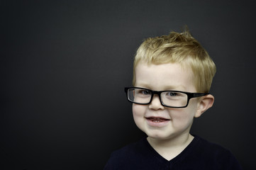 Smart young boy wearing glasses infront of a blackboard