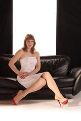 Frau im weißen Kleid auf Ledersofa sitzend