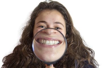 Girl smiling and show teeth through a magnifying glass