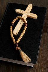 Bible, rosary and cross on wooden table close-up