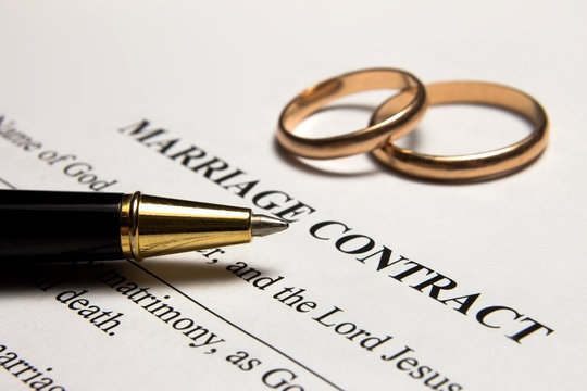 Pen and gold rings on the marriage contract
