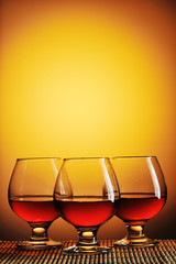 Three glasses of cognac on yellow background
