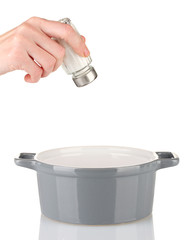Hand adding salt using  salt shaker isolated on white