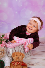 cute baby girl sitting in white basket