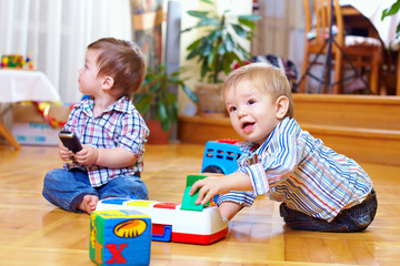 two baby boys playing with toys at home