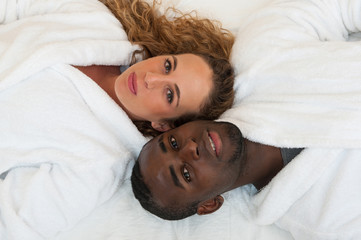 Happy young interracial couple lying in bed, top view.